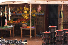 Fruit stand with plantain and sukuma (kale), amongst other things. The black metal objects are little charcoal-fueled stoves. It's called a Jiko and lots of Kenyans use this to cook on.